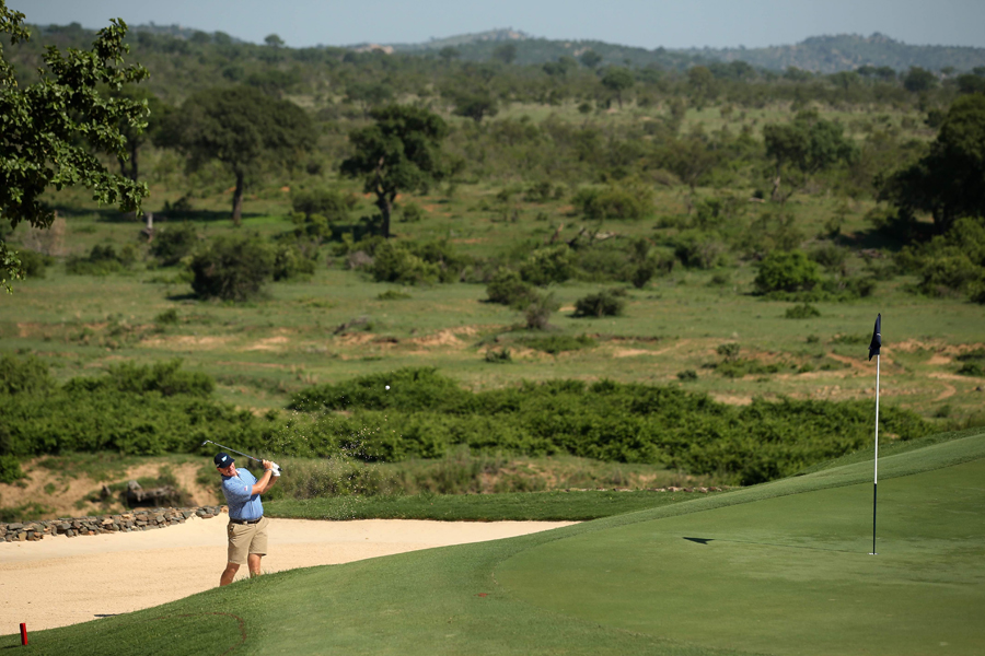 Ernie Els playing from the bunker alongside the iconic 13th green at Leopard Creek, which overlooks the vast bushveld expanse of the Kruger National Park.